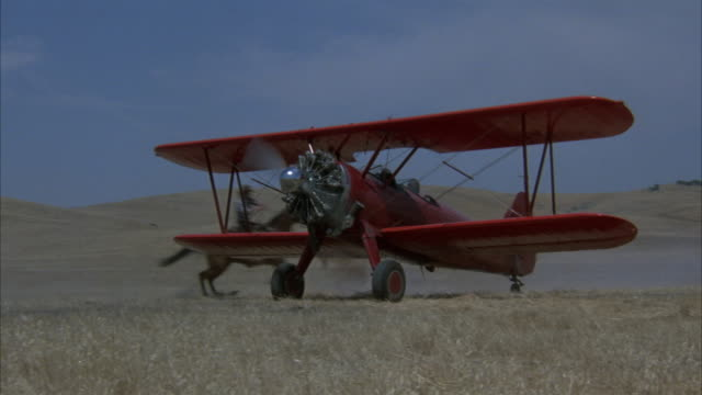 close angle of biplane or airplane landing on barn from right to left. cow moves to right, cowboys surround plane as it stops. dirt on film. hills in background. - scheune stock-videos und b-roll-filmmaterial