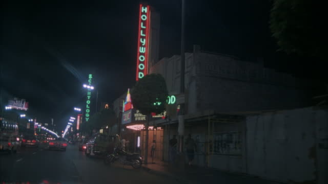"vidéos et rushes de 3/4 side process plate of hollywood blvd from car interior. pass ""hollywood"" movie theater featuring ""topgun"". green neon sign reads ""scientology"" ahead. - hollywood california"
