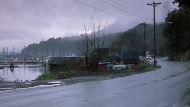 medium 3/4 side angle of lake road. white van appears from right and moves left along road. lake houses, sailboats on left. mountains and electrical wires in background. - lake van stock videos and b-roll footage