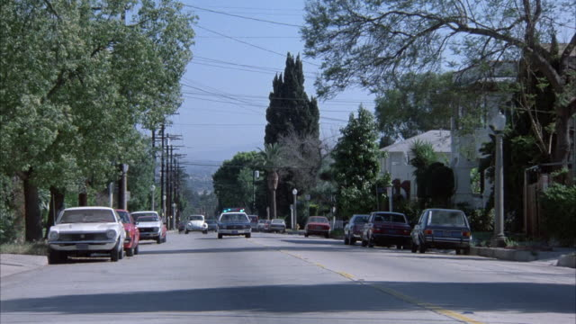 """vidéos et rushes de medium angle of street in residential area near hollywood. police car appears from distance in center approaching camera in middle of road. police car passes camera to right, rear of police car heading north. """"hollywood"""" sign on hills in background. yello - hollywood california"""