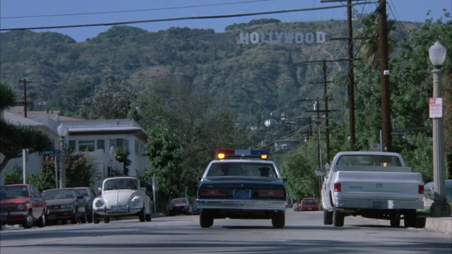 "medium angle of street in residential area near hollywood, ""hollywood"" sign on hills in background.  police car appears from bottom center approaching hollywood hills. cars on street, trees, palm trees, parked cars, electrical wires, two story houses on s - 1986 stock-videos und b-roll-filmmaterial"
