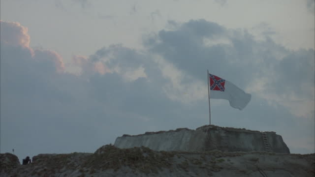 established medium angle of confederate flag on beach fort, flutters in wind. - confederate states of america stock videos & royalty-free footage