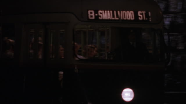 "MEDIUM ANGLE OF STREET CAR APPROACHING CAMERA AT NIGHT. SIGN READS ""8 - SMALLWOOD ST."" PANS RIGHT AND TRACKS STREET CAR PASSENGERS HOLDING AMERICAN FLAGS AND STANDING."