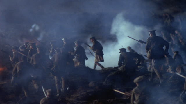 pan left to follow world war i era allied soldiers emerging from trenches and into battle. see groups of soldiers climbing over hills with rifles in hand.  rockets explode, causing fires and smoke. clouds of smoke partially obscure view. action. battlefie - prima guerra mondiale video stock e b–roll