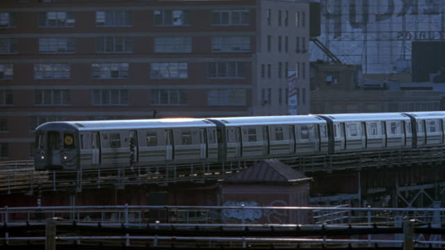 medium angle of elevated train approaching down tracks. see urban area and new york city skyline in background. - 1994 stock videos and b-roll footage