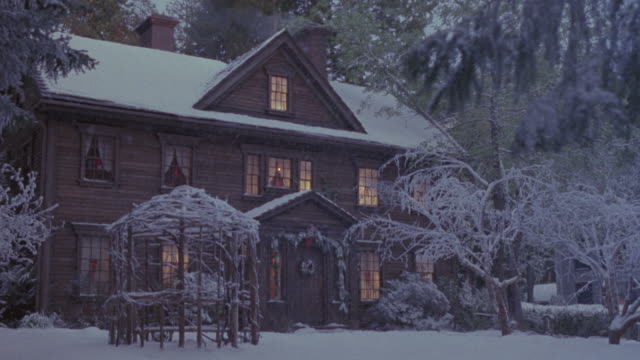 medium angle of large two story cabin house with attic. see christmas garland around entrance, wreath on door and snow covering roof, trees and ground. also see lights on inside. - 小屋点の映像素材/bロール