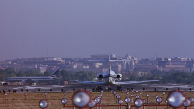wide angle of runway with plane taxiing in background. see runway lights and tail end of another airplane in foreground. also see buildings and city skyline in background. - airplane tail stock videos and b-roll footage