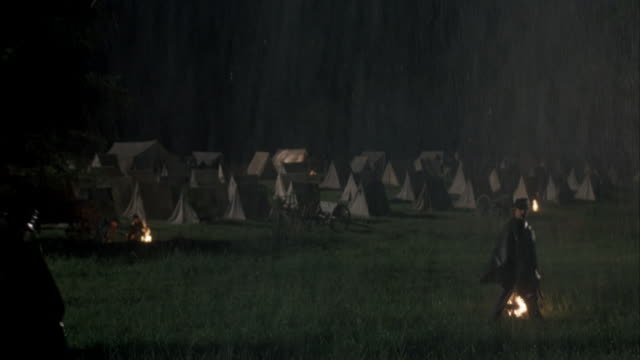 wide angle of soldier camp with guard on watch in heavy rain. see tents and fires. see guard walk right as marching troop approaches and passes. see guard begin to pace back and forth carrying gun on back. neg cut. - festzelt stock-videos und b-roll-filmmaterial
