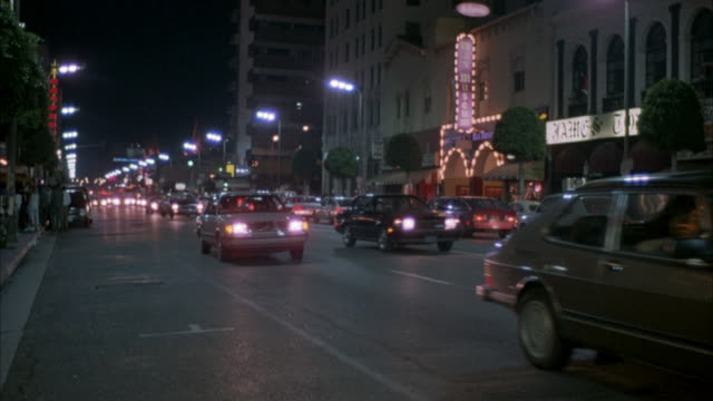 pan right of city street lit by street lamps and store signs. see traffic passing in both directions. follows approaching police car into foreground. - 1986 stock videos and b-roll footage