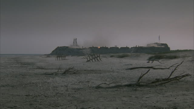 MEDIUM ANGLE OF FORT ON BEACH. SEE FLAG STICKING OUT OF FORT. SEE SMOKE FROM CANNONS BEING FIRED. SEE CANNONS OFF SCREEN FIRING ONTO FORT AND INTO SAND. SEE PEOPLE ON TOP OF FORT. SEE TREE BRANCHES STICKING OUT OF THE SAND. SKY IS OVERCAST AND GRAY. ACTIO