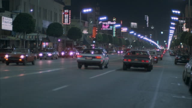 stockvideo's en b-roll-footage met medium angle of cars driving down hollywood boulevard lit by street lamps and store signs. see opposing traffic. pans left to follow approaching police car. pans right. - hollywood california