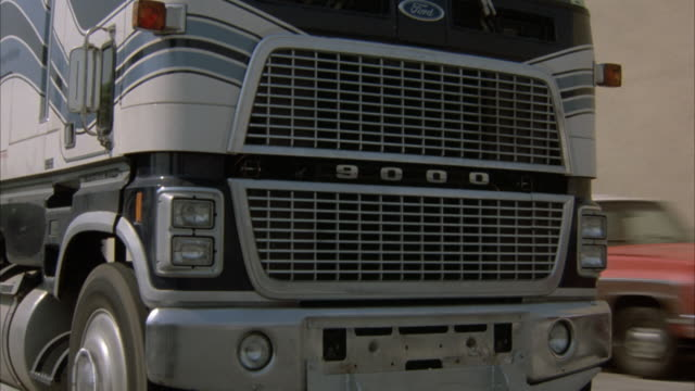 medium angle of radiator grille on ford 9000 gasoline tanker truck. see entire length of tanker as it passes by. see small toll booth, electric poles and lines and semi trucks in the background. - ford truck stock videos and b-roll footage