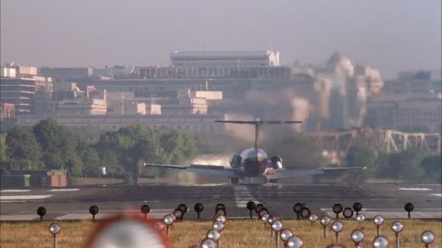 "medium angle pov on grass behind runway. see landing lights leading up to runway in foreground. see twin engine commercial airliner, airplane, plane or jet enter at top of screen and land on runway. see ""american"" airlines jet taxi into screen from left a - landen stock-videos und b-roll-filmmaterial"