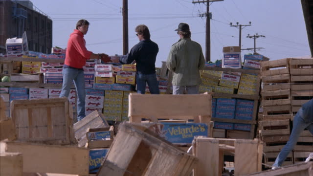 medium angle of four young men unloading crates and boxes in an assembly line process. see man in black shirt run across in foreground. see leftmost man of four jump and push the rest out of the way as a black car drives through. see boxes and contents fl - schwarzes hemd stock-videos und b-roll-filmmaterial