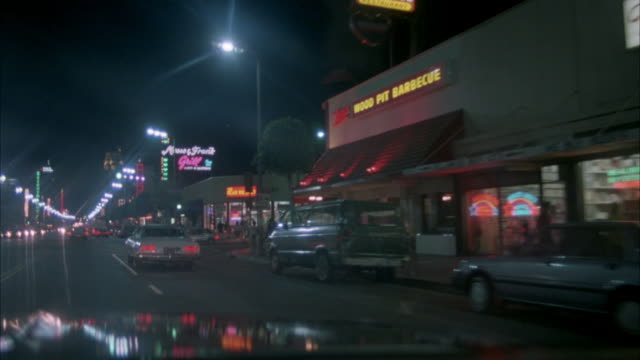 "stockvideo's en b-roll-footage met wide angle driving pov straight forward from passenger side. traveling down hollywood blvd. see front hood. see signs for restaurants ""wood pit barbecue"", ""musso & frank grill"", and ""vogue"" movie theater. sometimes see pov change to front passenger window - hollywood california"
