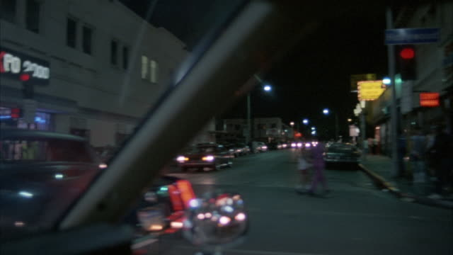 "WIDE ANGLE DRIVING POV STRAIGHT FORWARD FROM PASSENGER SIDE. TRAVELING DOWN HOLLYWOOD BLVD. SEE FRONT HOOD. POV IS FROM FRONT PASSENGER WINDOW. SEE SIGN FOR ""HOLLYTRON"". SEE GLARE FROM STREET LAMPS. POV CHANGES TO FRONT WINDSHIELD. SEE COUPLE ON MOTORCYCL"