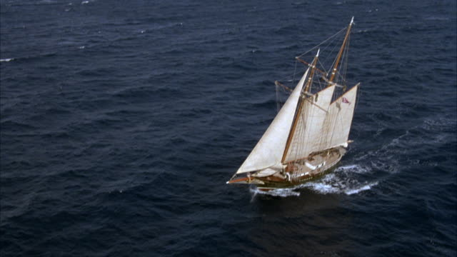 aerial tracking shot of two mast wooden sailing ship or sailboat sailing in open ocean. sailboat has two white main sails and two white jib sails. sailboat is moving from right to left. see boat rocking up and down with ocean swell. see flag flying from m - mast sailing stock videos & royalty-free footage