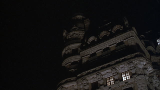 """medium angle pan down from elevated pov of ansonia hotel or possibly apartment building. hotel is stone building with ornate stone carvings. see full moon above building. pov pulls back and then zooms in on side of hotel.<p><a href=""""https://www.sonypictur - https点の映像素材/bロール"""