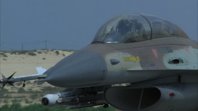 MEDIUM ANGLE OF LEFT SIDE OF A CAMOUFLAGE MILITARY F-16 FIGHTER JET AIRPLANE. SEE PILOT. SEE GLASS WINDSCREEN RAISE. FADES TO A BLUR. MIDDLE EAST.