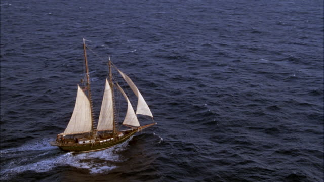 aerial tracking shot of two mast sailing ship or sailboat sailing in open ocean.  sailboat has main sail, fore sail, jib and flying jib which are all white. pov circles the boat clockwise from starboard to port side. see boat rocking up and down with ocea - dondolarsi video stock e b–roll