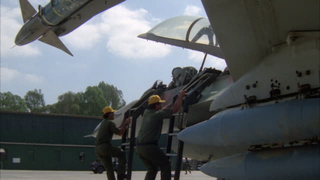 MEDIUM ANGLE OF SIDE VIEW OF SIDE OF CAMOUFLAGE MILITARY F-16 FIGHTER JET AIRPLANE. SEE PILOT. SEE MISSILE AT TOP. SEE CREW WITH YELLOW HATS AND OLIVE JUMPSUITS COME TO MAKE FINAL PREPARATIONS AND REMOVE LADDERS TO PLANE. SEE GLASS WINDSCREEN CLOSE. SEE C