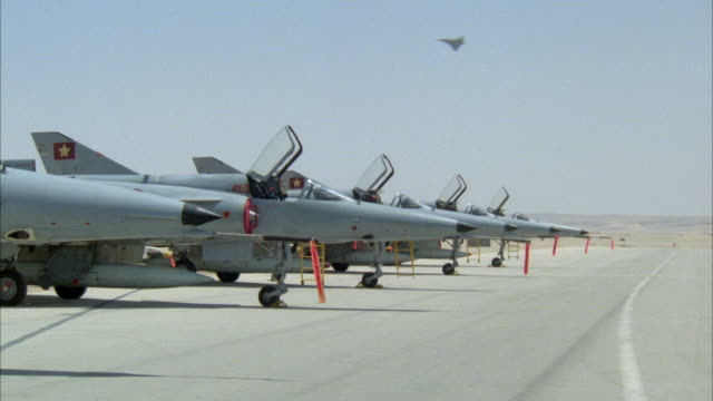 MEDIUM ANGLE OF ROW OF MILITARY F-16 FIGHTER JET AIRPLANES ON GROUND WITH GLASS WINDSCREENS UP. SEE JET FLY BY IN THE BACKGROUND. SEE SOLDIERS ENTER AND START RUNNING TOWARD PLANES. SEE MILITARY JEEP ENTER CARRYING SEVERAL PILOTS WHO JUMP OFF AND RUN TOWA