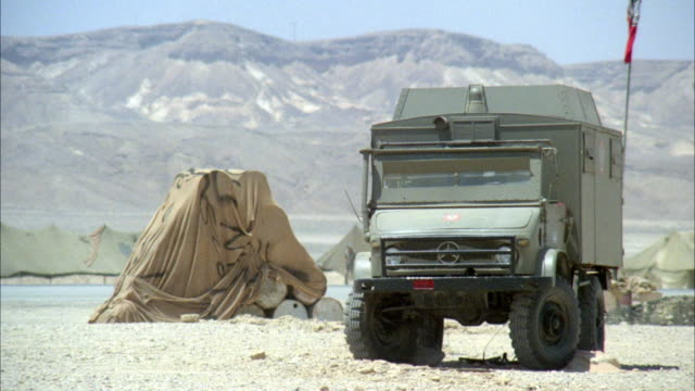 medium angle of mercedes military truck with red flag on top. see pile of barrels covered by a tarp. see tents pitched and soldiers running in background. see mountains in background. see barrels and truck explode and burst into flames with pieces falling - armé bildbanksvideor och videomaterial från bakom kulisserna
