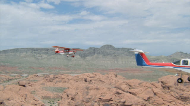 aerial of small red, white and royal blue passenger plane flying over rocky plains area with sparse vegetation. then see small red and white passenger plane approach other plane from behind. focuses on red and white plane flying over mountains. neg cut. - royal blue stock videos & royalty-free footage