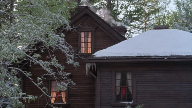 vidéos et rushes de medium angle of two story wooden cabin surrounded by trees and with snow on roof. pov zooms in on silhouette of person walking by window on second floor. see smoke coming from chimney of house. - zoom avant
