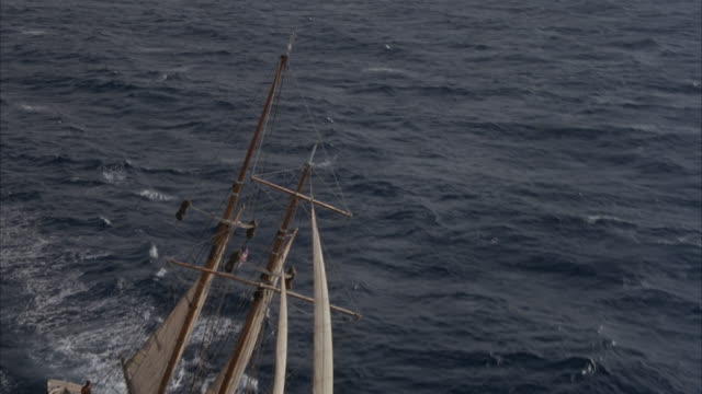 aerial tracking shot of two mast wooden sailing ship or sailboat sailing in open ocean.  sailboat has main sail, fore sail, jib and flying jib which are all white. pov circles the boat clockwise from starboard to port side. see boat rocking up and down wi - dondolarsi video stock e b–roll