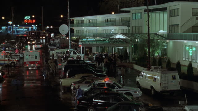 medium angle from elevated pov over parking lot behind emergency entrance to hospital. see emergency entrance to hospital on right with crowd of people at doors. see parking lot full of cars including news vans, ambulances and police car with bizbar light - 1999 stock videos & royalty-free footage