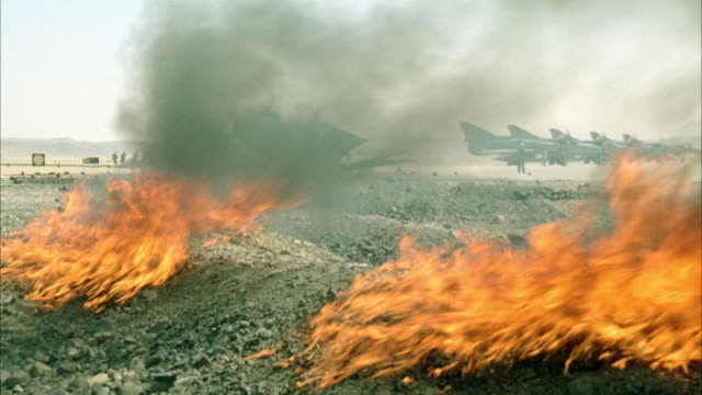 MEDIUM ANGLE OF TWO FIRES RAGING IN PILE OF GRAVEL. SEE F-16 FIGHTER JET PLANES IN BACKGROUND. SEE SOLDIERS RUN PAST IN BACKGROUND WHEN TWO SOLDIERS COME TO LOOK AT FIRES. MIDDLE EAST.