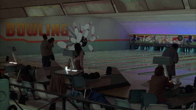 "vídeos de stock, filmes e b-roll de medium angle of several people bowling on bowling lanes at bowling alley. see large sign ""bowling"" on far wall. pov is focused on people and not on lanes or pins. see people stop bowling and walk towards left away from lanes to see something that is happe - cancha de jogo de boliche"