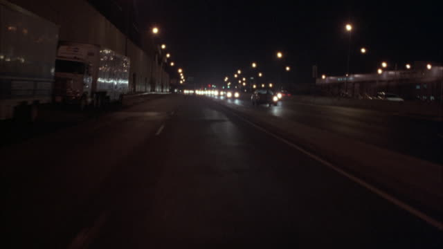 process plate straight back driving on city street in urban area with many other cars behind pov. see stores and dark buildings on left side of screen. see divider on right between opposing directions of traffic. - anno 1994 video stock e b–roll