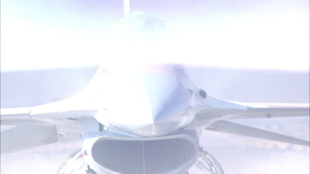 MEDIUM ANGLE OF A CAMOUFLAGE MILITARY F-16 FIGHTER JET AIRPLANE ON THE GROUND. POV IS DIRECTLY IN FRONT OF JET FACING THE PILOT. SEE PILOT WITH FACE MASK AND HELMET. SEE PILOT NOD HIS HEAD SEVERAL TIMES. SEE GRAY SMOKE PASSING IN BACKGROUND. MIDDLE EAST.