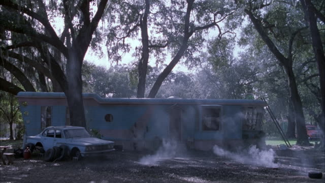 MEDIUM ANGLE OF LOWER CLASS BLUE MOBILE HOME OR SMALL HOUSE SURROUNDED BY TREES. SEE BROKEN DOWN BLUE CAR ON LEFT OF HOUSE. SEE LEFT SIDE OF HOUSE EXPLODE IN BALL OF FIRE SENDING DEBRIS FLYING. EXPLOSIONS.