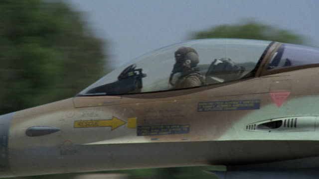 MEDIUM ANGLE OF A CAMOUFLAGE MILITARY F-16 FIGHTER JET MOVING DOWN RUNWAY. SEE FIELD AND GRASS IN BACKGROUND. SEE PILOT WITH FACE MASK AND HELMET ON. POV IS FROM SIDE OF JET. PANS RIGHT TO FOLLOW NEXT F-16 FIGHTER JET MOVING DOWN RUNWAY. SEE PILOT LOOKING
