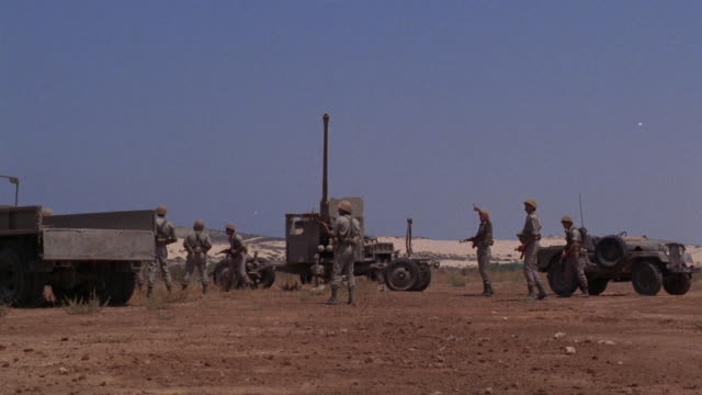 wide angle of soldiers standing on field armed with guns. see military truck, tank and jeep in background. see one soldier point up towards the sky. see explosion right above right above their heads and produce thick white smoke. see soldiers start runnin - esercito video stock e b–roll