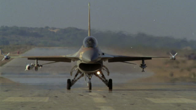 MEDIUM ANGLE OF A CAMOUFLAGE MILITARY F-16 FIGHTER JET APPROACHING DOWN RUNWAY. SEE FIGHTER PILOT WITH HELMET AND FACE MASK ON. POV IS FROM DIRECTLY IN FRONT OF JET. SEE JET TURN RIGHT. SEE TWO PILOTS IN JET. THEN SEE JET TURN LEFT. NEG CUT. MIDDLE EAST.