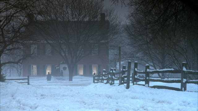 medium angle of two story brick house with snow covering ground. see bare trees in front of house. see white picket fence around house. see two people by door of house hanging something and another person standing by fence in front of house. see horse dra - brick house stock videos & royalty-free footage