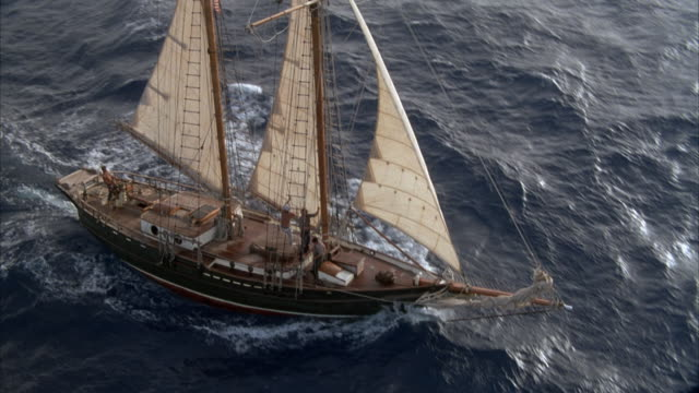 aerial tracking shot of two mast sailboat or sailing ship sailing in open ocean. see three white sails powering boat. see three sailors towards bow, one of which is climbing rigging of front mast. see man at helm at stern. pov pulls back and boat moves aw - marinaio video stock e b–roll
