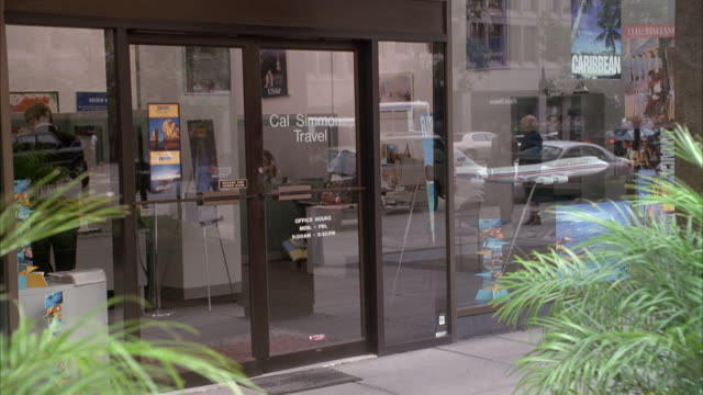 "medium angle establishing shot of glass doors to ""cal simmon travel"" agency. storefront is all glass, see reflection of pedestrians and other buildings in glass. see ferns or bushes in foreground. - building entrance stock videos & royalty-free footage"