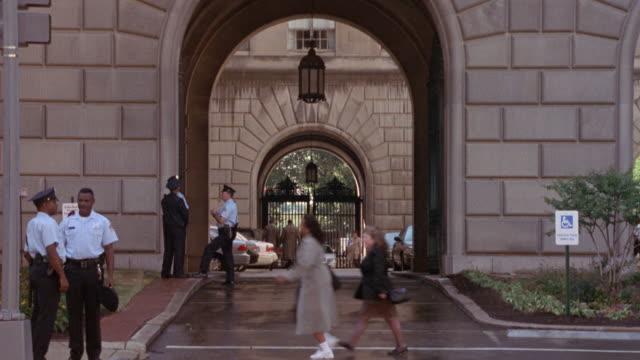 medium angle of arch or gate at government building, security guards stand around. two men walk into frame, then green jaguar car drives from back through gate, pov tracks as car drives right onto street. three men in suits cross street with government bu - 門点の映像素材/bロール