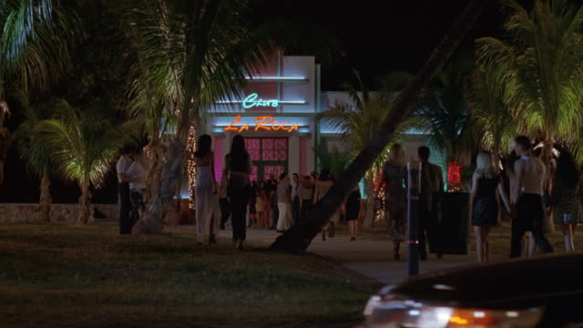 "wide angle of entrance to nightclub, neon lights read ""club la roca."" cars drive by on street as people walk up to nightclub, man and woman, couple at left kiss one another. could be south beach area. bars. - マイアミ点の映像素材/bロール"