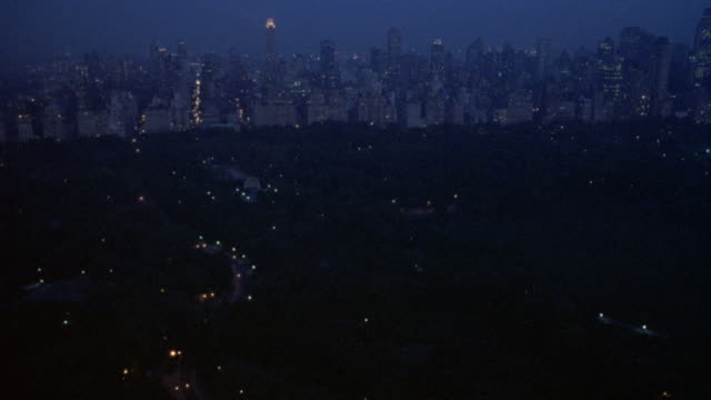 aerial over central park, zooms in on apartment building, then pulls back and zooms in on another apartment building. - 1994 stock-videos und b-roll-filmmaterial