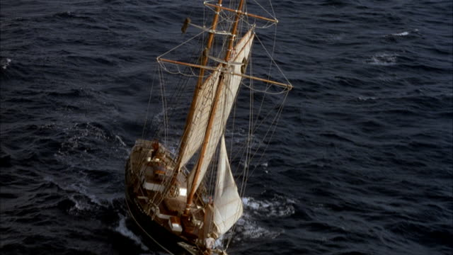 aerial tracking shot of wooden two mast sailboat or sailing ship sailing in open ocean. see four white sails powering boat. see american flag flying from mast. boat is moving up and down with ocean swells. pov starts in close on sails and masts and pulls - schiffsmast stock-videos und b-roll-filmmaterial