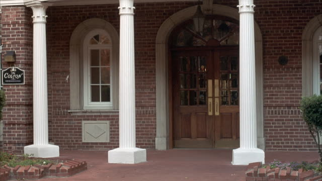 "medium angle establishing shot of entrance to brick house or building. see three small white columns in front of front door. see small sign on left, ""colton."" - brick house stock videos & royalty-free footage"