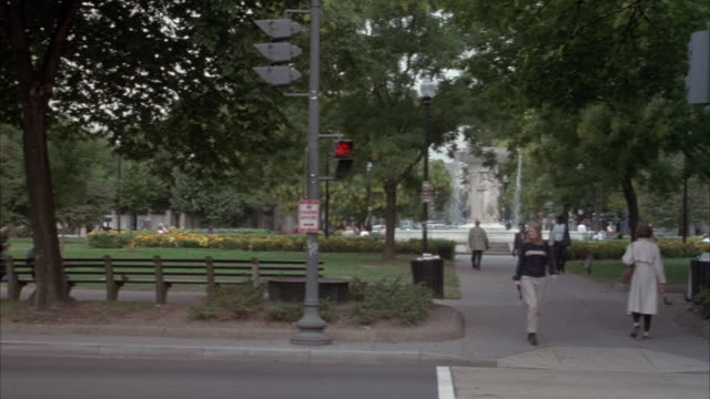 medium angle of dupont circle with dupont fountain in center. pov pans left to track silver 1999 ford taurus from left to right in city street in foreground. see washington club, private social organization, or patterson house building at end. - dupont circle stock videos & royalty-free footage