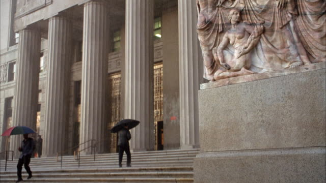 medium angle of entrance leading up to stone building with large stone columns, probably government building.  see stone carving on relief on right. see people walking up stairs on left to entrance with umbrellas. raining. - relief carving stock videos & royalty-free footage