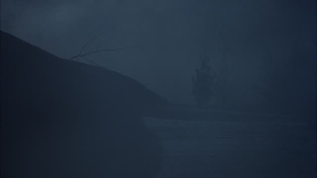 """tracking shot of taxi driving on snow covered mountain road in fog. see car sliding or skidding all over road from snow. pov pans right as taxi moves towards pov, see trees in foreground. see taxi crash into snow bank on left side of road. see ad for """"sen - nebbia video stock e b–roll"""